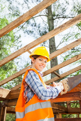 Female Worker Cutting Wood With Handsaw At Site