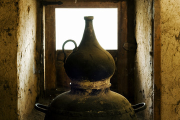traditional alembic distiller with window in old adobe  house