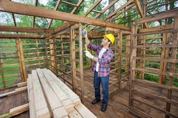 Worker Taking Measurements In Timber Cabin