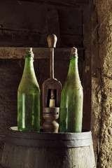 antique wooden wine corker and two  bottles in old adobe house