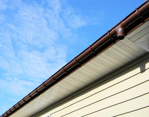 A newly installed modern rain gutter against blue cloudy sky
