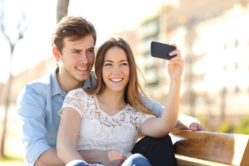 Couple photographing a selfie with a smart phone in a park