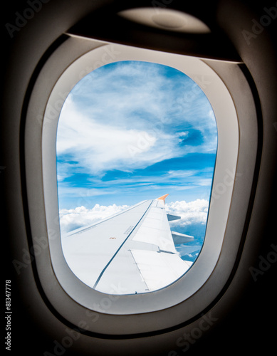 Aluminium Singapore Looking through window aircraft during flight in wing with blue