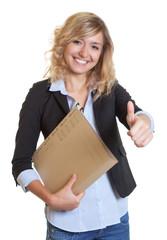 Blonde Sekretärin mit Akte zeigt den Daumen