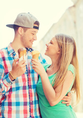 smiling couple with ice-cream in city