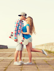 smiling couple with skateboard kissing outdoors