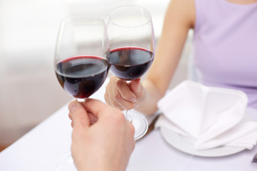 young couple with glasses of wine at restaurant