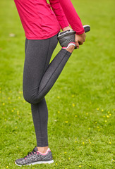 close up of woman stretching leg outdoors