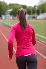 woman running on track outdoors from back