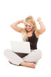 Happy blonde woman sitting on the floor with notebook over white
