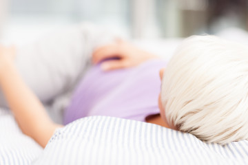 Blonde woman is lying in the bed at home