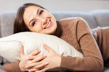 Caucasian woman is smiling towards the camera while hugging a pi