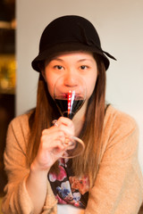 Cute Asian Girl drinking a Glass of red Wine