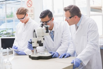 Scientists examining something with the microscope