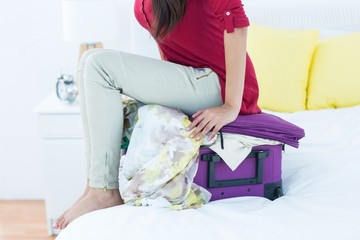 Woman sitting down on top of her suitcase