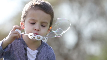 Cute little boy, playing with soap bubbles in the park
