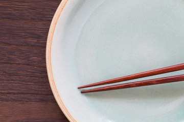Wood brown chopsticks and celadon ceramic on wood table