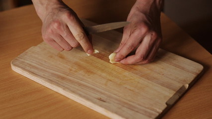 man on a kitchen board cuts garlic