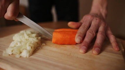man on a kitchen board cuts carrots