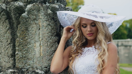 Modest bride in a white hat looking at camera