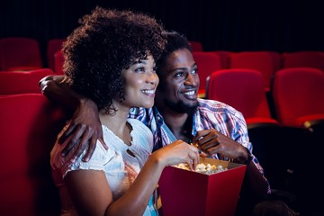 Happy young couple watching a film