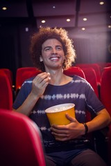 Smiling young man watching a film