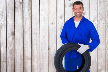 Composite image of mechanic holding tire on white background