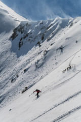 Backcountry skier on a windy mountain slope