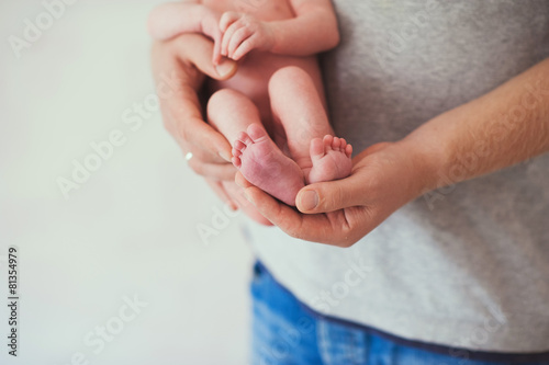 Newborn baby feet on father  hands, close-up - 81354979