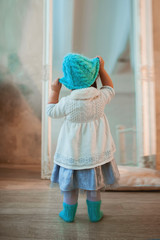 Little girl standing with her back to the mirror and trying to r