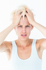 Sad blonde woman with head pain holding her head