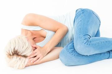 Sad blonde woman lying on the floor