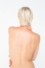 Beautiful topless woman touching her back