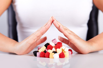 Female hands over a pyramid of candies