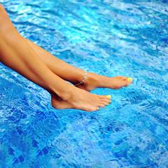 Woman legs in a swimming pool