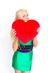Blonde Frau mit Herzkissen in der Hand