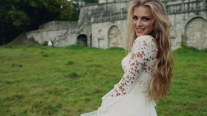 Dynamic video of a beautiful blonde in white dress with long