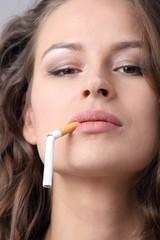 Frau mit durchgebrochener Zigarette im Mund