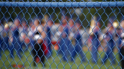 Marching Band Out Of Focus Behind Fence