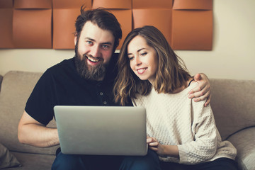 Happy couple in a new living room shopping online with laptop
