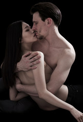 Bare-chested lovers cuddling on black background