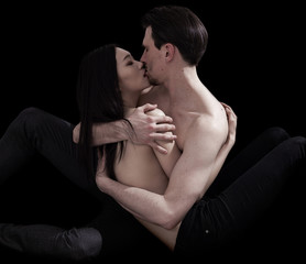 Bare-chested lovers hugging on black background