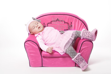 Baby mit rosa Kleid schläft auf einem rosa Sessel