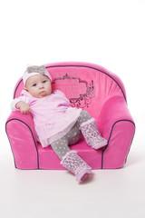 Baby mit rosa Kleid auf einem rosa Sessel