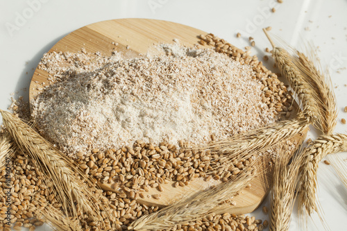 wheat flour of a rough grinding. Grain and spikelets on table