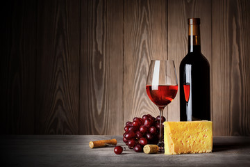 Bottle and glass of red wine with cheese grapes and corkscrew