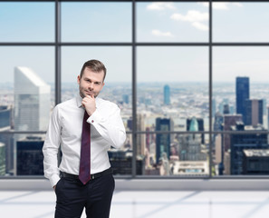 Young businessman is standing in a panoramic New York office