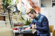 Leinwanddruck Bild - Young handsome man soldering a circuit board