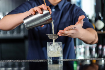 Barman makes cocktail in a bar