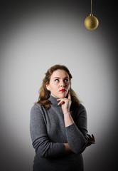 Girl in grey and Christmas ball.